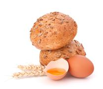bun with seeds and broken egg - stock photo