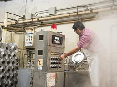 Hispanic worker operating machinery in textile factory Stock Photos