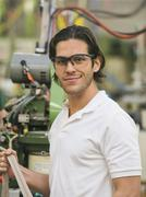 Mixed race worker smiling in textile factory Stock Photos