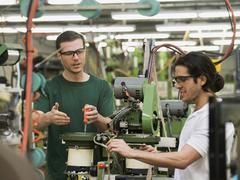 Workers operating machinery in textile factory Stock Photos
