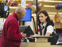 Cashier and customer at grocery store checkout Kuvituskuvat