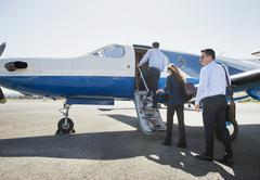 Business people boarding airplane on runway Stock Photos