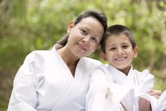 Hispanic mother and son wearing martial arts robes Stock Photos