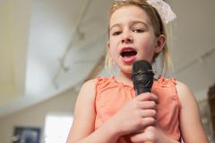 Caucasian girl singing karaoke at home Stock Photos