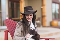 Caucasian woman petting dog in armchair Stock Photos