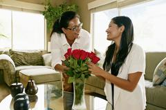 Mother and daughter arranging flowers in vase Stock Photos