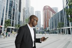 Black businessman using cell phone on city street, Beijing, Beijing, China Stock Photos