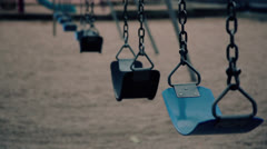 Empty swings on a playground - stock footage