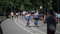 Bicycle riders and joggers in New York Central Park Stock Footage