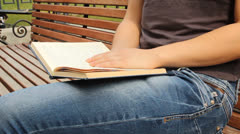 A young girl reading a book on a bench. Summer city park Stock Footage