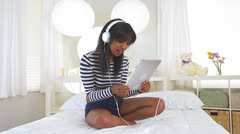 Cute black girl listening to headphones and having video chat on tablet Stock Footage