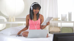 Black girl listening to music while using laptop and watching tv Stock Footage