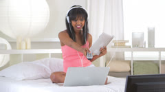 Black girl changing channel while using tablet and laptop computer Stock Footage
