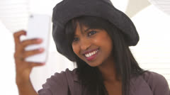 Black girl taking self shots with phone while wearing stylish hat Stock Footage