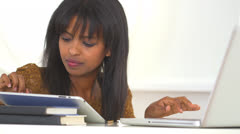 African American college student talking on cell phone while studying Stock Footage