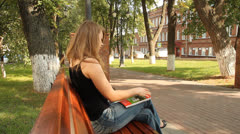 Young girl reading a glossy magazine in the park Stock Footage