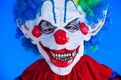 scary clown person in clown mask on blue background - stock photo