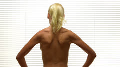 Rear view of blonde woman flexing back muscles Stock Footage