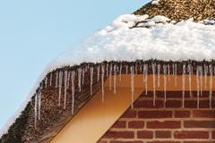 Icicles hanging on the roof of an old dutch farm Stock Photos