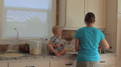 A baby boy and his mother in kitchen Stock Footage