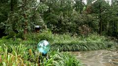 Blue garden orb rain stone path Stock Footage