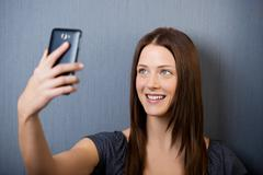 beautiful young female clicking picture of herself - stock photo