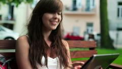 Female student with tablet computer sitting in city park HD Stock Footage