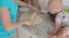 A mother and baby making pizza Stock Footage