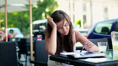 Angry, overwhelmed female student sitting in cafe HD Stock Footage