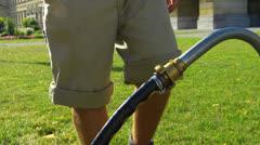 Gardener unplug water hose from underground pipe in Park - stock footage