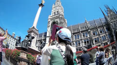 Fisheye Asian tourist filming Munich Town Hall with Tablet PC as camera Stock Footage