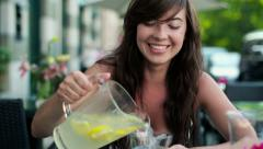 Woman pouring fresh lemonade into glass in cafe HD Stock Footage