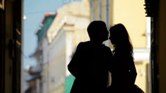 Outlines of a loving couple standing in the passage between the houses Stock Footage