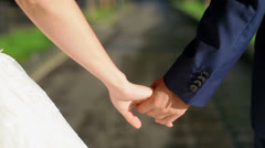 Newly married couple walk together holding hands Stock Footage