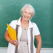 senior woman holding file against chalkboard - stock photo