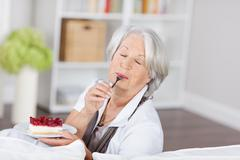 senior woman enjoying a fruity cream cake - stock photo