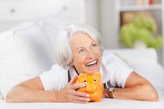 Smiling senior woman with a piggy bank Stock Photos