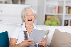 laughing beautiful senior with a tablet-pc - stock photo