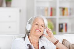 Stock Photo of modern senior woman listening to music
