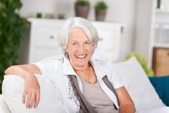 Senior woman sitting on sofa at home Stock Photos