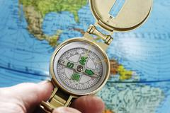 Person holding compass, globe in background, close-up Stock Photos