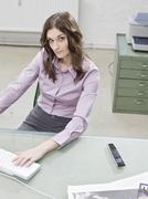 Young businesswoman working in office, elevated view - stock photo