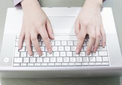 Woman typing on computer, elevated view - stock photo
