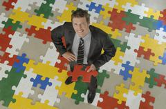 Business man standing on jigsaw puzzle, holding piece of puzzle, smiling, - stock photo