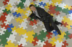 Businessman lying on jigsaw puzzle, holding piece of puzzle, smiling, portrait, - stock photo