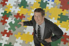 Businessman standing on jigsaw puzzle, holding piece of puzzle, smiling, - stock photo