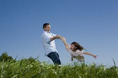 Stock Photo of Father and daughter (6-7) having fun in the meadow