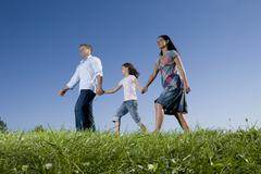 Parents and daughter (6-7) taking a walk across meadow Stock Photos