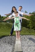 Young family balancing on boardwalk in a playground Stock Photos
