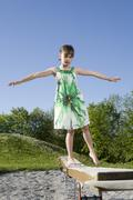 Young girl (7 years) balancing on boardwalk in a playground - stock photo